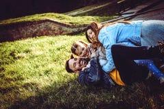 играть семьи счастливый напольный Семья лежа и играя на gr Стоковая Фотография