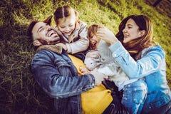 играть семьи счастливый напольный Семья лежа и играя на gr Стоковые Изображения RF