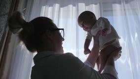 Играют хорошие родителей, мама с маленьким сыном в оружия внутри помещения против окна сток-видео