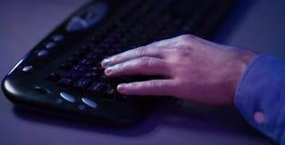 Играющ игры онлайн Рука Gamer на клавиатуре стоковые фотографии rf