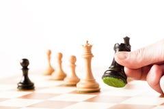 Играющ шахмат - грачонка руки moving черный на доске Стоковое фото RF