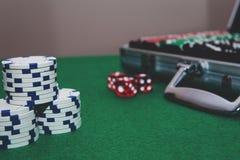 Играя в азартные игры концепция с покером чемодана на зеленой таблице с dices и белые обломоки стоковая фотография