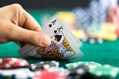 Играя в азартные игры рука держа самую лучшую серию карточки игры и обломоки денег Стоковые Изображения