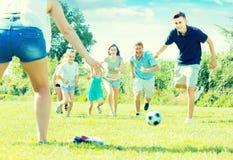 Играя в азартные игры люди семьи из шести человек счастливо играя в togeth футбола Стоковая Фотография RF