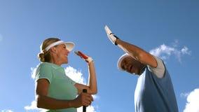 Играя в гольф пары высоко fiving на поле для гольфа видеоматериал