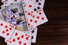 Играя карточки, кость и 100 долларовых банкнот на темном woode Стоковые Фото
