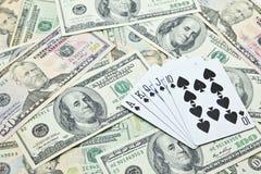 Играя карточки на куче банкнот доллара США Стоковая Фотография RF