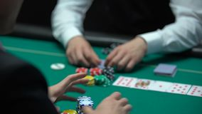 Игра в покер, игрок имеет выигрывая карточки комбинацию, держит пари все ключи наличных денег и дома сток-видео