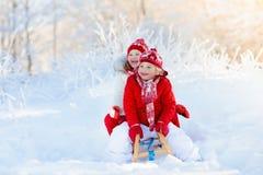 Игра детей в снеге Езда саней зимы для детей Стоковые Фото