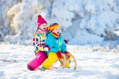 Игра детей в снеге Езда саней зимы для детей Стоковые Фотографии RF