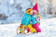 Игра детей в снеге Езда саней зимы для детей Стоковая Фотография RF