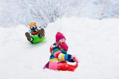 Игра детей в снеге Езда скелетона зимы для детей стоковые изображения rf