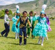 Игра детей в традиционных костюмах Kazahk Стоковое Фото