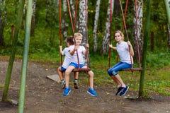 Игра детей на качаниях летом стоковое фото rf