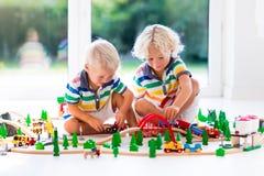Игра детей с поездом игрушки Ягнит деревянная железная дорога Стоковые Изображения