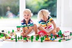 Игра детей с поездом игрушки Ягнит деревянная железная дорога Стоковая Фотография RF