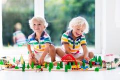 Игра детей с поездом игрушки Ягнит деревянная железная дорога Стоковая Фотография
