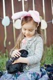 Игра детей с реальным кроликом Смеясь над ребенок на пасхальном яйце охотится с белым зайчиком любимчика Маленькая девушка малыша Стоковая Фотография