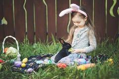 Игра детей с реальным кроликом Смеясь над ребенок на пасхальном яйце охотится с белым зайчиком любимчика Маленькая девушка малыша Стоковое фото RF