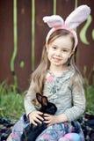 Игра детей с реальным кроликом Смеясь над ребенок на пасхальном яйце охотится с белым зайчиком любимчика Маленькая девушка малыша стоковая фотография rf