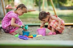 Игра 2 девушек в ящике с песком Стоковое фото RF