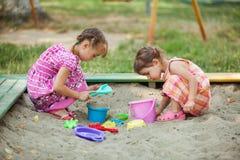 Игра 2 девушек в ящике с песком Стоковые Изображения RF