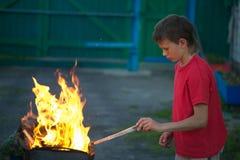 Игра детей с огнем в гриле Стоковая Фотография
