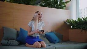 Игра женщины и ослаблять в современном офисе Молодая официально женщина в юбке охлаждая на софе в современном офисе сток-видео