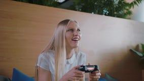 Игра женщины и ослаблять в современном офисе Молодая официально женщина в юбке охлаждая на софе в современном офисе акции видеоматериалы