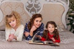 Игра красивых детей в их пижамах на кровати перед goin Стоковое Изображение