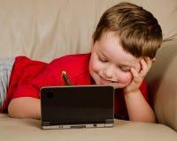 игра кресла принципиальной схемы мальчика играя видео картошки Стоковое Изображение