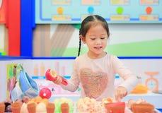 Игра маленькой девочки претендует как продажа в магазине мороженого стоковое изображение rf