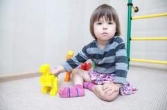 Игра маленькой девочки при figurines динозавра сделанные пластичным блоком конструктора забавляется Стоковое Изображение RF