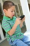 игра мальчика играя видео Стоковое Изображение