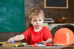 Игра мальчика ребенк как разнорабочий Концепция детства Малыш на занятой стороне играет с инструментами дома в мастерской Ребенок стоковые фотографии rf