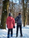 Игра 2 мальчиков с снегом в парке зимы Стоковая Фотография