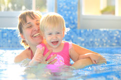 Игра матери с ее ребенком в плавательном бассеине Стоковые Изображения