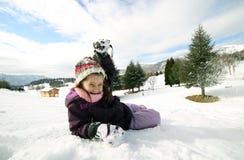 Игра маленькой девочки с снегом в горах в зиме Стоковые Фотографии RF