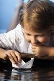 Игра мальчика в бумажном корабле стоковые фотографии rf