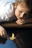 Игра мальчика в бумажном корабле стоковая фотография rf
