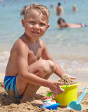 Игра мальчика на пляже th Стоковое Фото