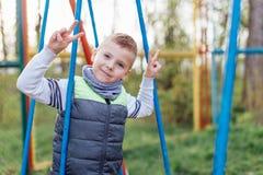 Игра мальчика на спортивной площадке с предпосылкой парка нерезкости Стоковое фото RF