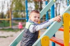 Игра мальчика на спортивной площадке с предпосылкой парка нерезкости Стоковая Фотография
