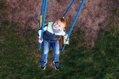 Игра мальчика на спортивной площадке с предпосылкой парка нерезкости Стоковое Изображение RF