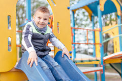 Игра мальчика на спортивной площадке с предпосылкой парка нерезкости Стоковые Фото