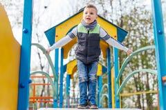 Игра мальчика на спортивной площадке с предпосылкой парка нерезкости Стоковые Изображения RF