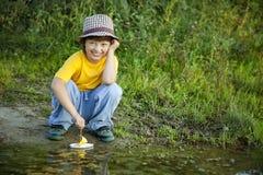 Игра мальчика с кораблем игрушки в воде, chidlren игра парка с шлюпкой внутри стоковое изображение