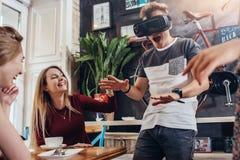 Игра молодого шлемофона виртуальной реальности испытания парня кричащая играя страшная пока его жизнерадостный довольно женский с стоковые изображения rf