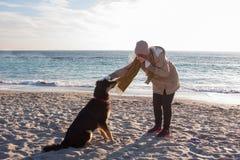 Игра молодой женщины с большой черной собакой Стоковые Фотографии RF