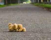 Игра опасности Плюшевый медвежонок лежит на дороге Стоковые Изображения